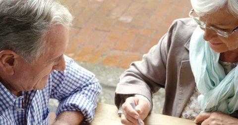 Senior woman feeding sweet food to senior man in outdoor caf? 4k
