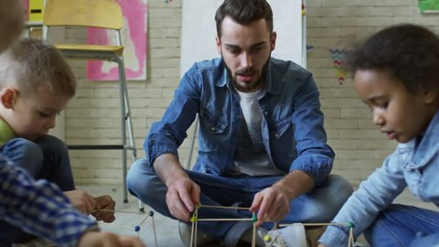 Man sitting on the floor with and talking to kids while they making cubes  with craft sticks and play dough
