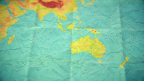 Zoom in from World Map to Australia. Old well used world map with crumpled paper and distressed folds. Muted vintage colors. Blank version