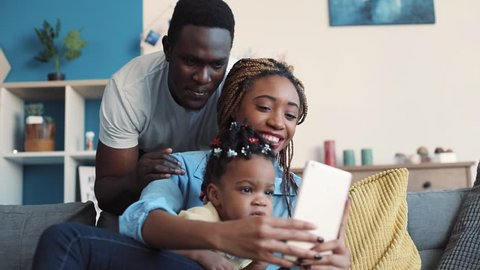 Cheerful African American family takes selfie in their cozy living room. Having fun, social networks, modern culture. Slow motion, close up view