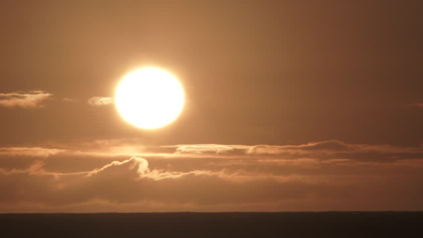 Close up on bright sun shining bright above cloudy ocean horizon near sunset. | Shutterstock HD Video #1008694036