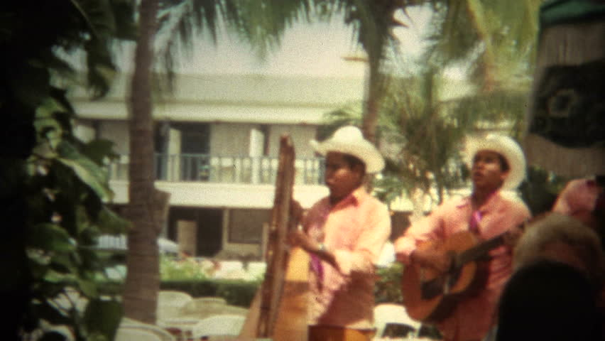 ACAPULCO, MEXICO - JANUARY 1971: Mexican mariachi band entertaining the tourists in a fancy resort in town.
