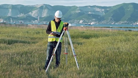 A male surveyor in work clothes adjusts the equipment on the construction site. The concept of landscape design, geodesy