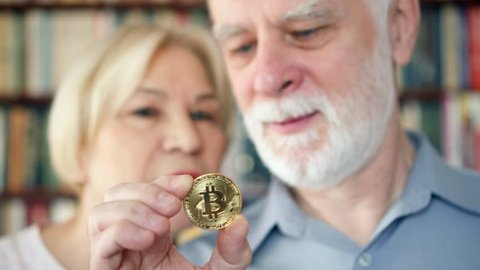 Senior couple holding and looking at cryptocurrency bitcoin. Shiny virtual money of online trade. Active modern life after retirement. Concept of pension savings and ebusiness. Focus on bitcoin