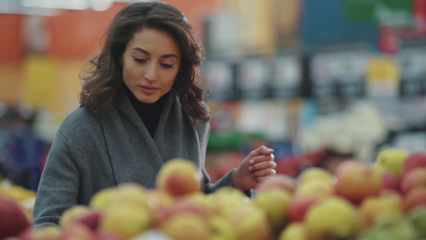 Serious young woman choosing apple at fruit vegetable supermarket marketplace lifestyle commerce product fresh hand customer food beautiful girl shopping selecting face buy store grocery holding | Shutterstock HD Video #1008728846