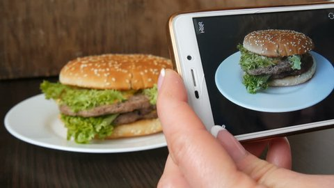 Female hand makes a photo on the smartphone of a beautiful juicy hamburger with lettuce leaves on a stylish wooden background