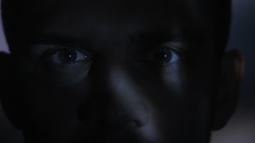 Close up eyes of a young man watching a video or film on TV or a computer monitor. Reflection on his face