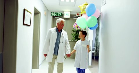 Doctor interacting with patient while walking in corridor at hospital