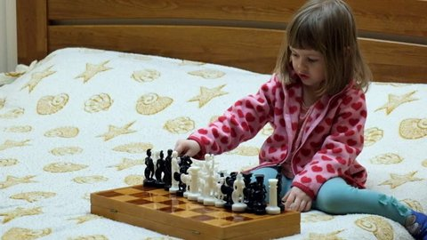 Little girl is playing chess