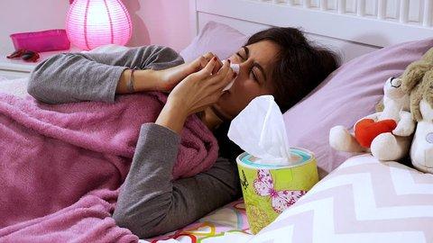 Cute female teenager lying in bed sneezing using handkerchief