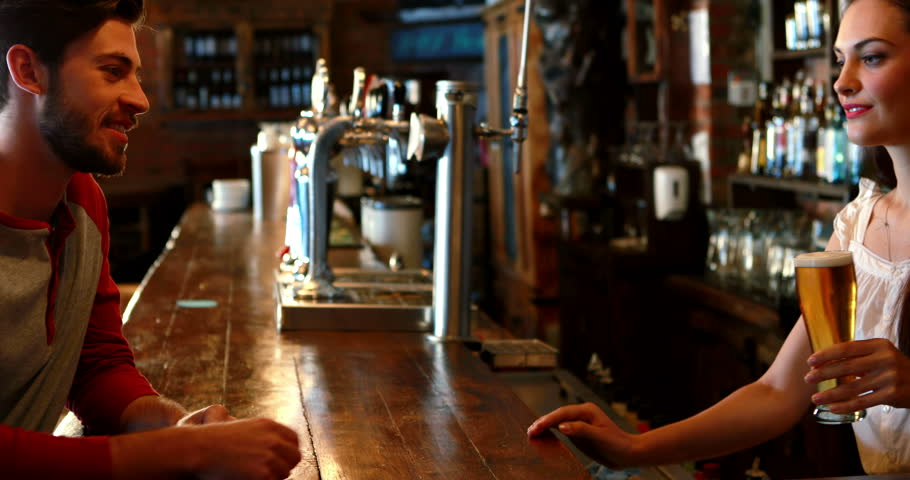 Barmaid interacting with male costumer while serving beer in pub | Shutterstock HD Video #1008767336