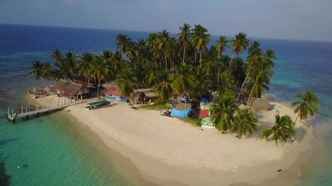 Aerial drone bird's eye view of tourists arriving on boat to San Blas Carribean paradise island with palms, bungalows and pier , left motion