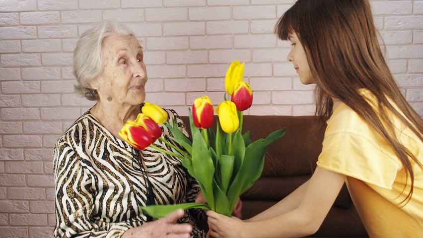 The child gives flowers. Granddaughter gives flowers to her grandmother.