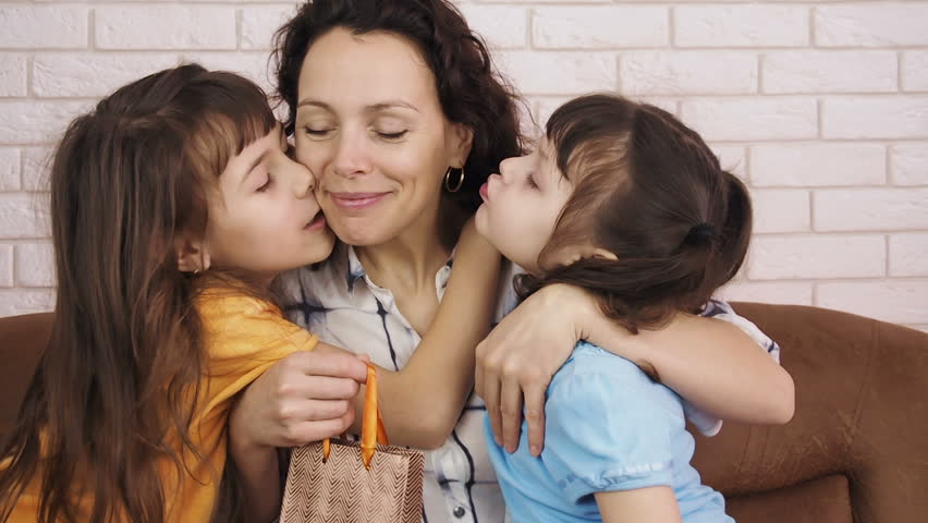 Mothers Day. Children kiss mom.