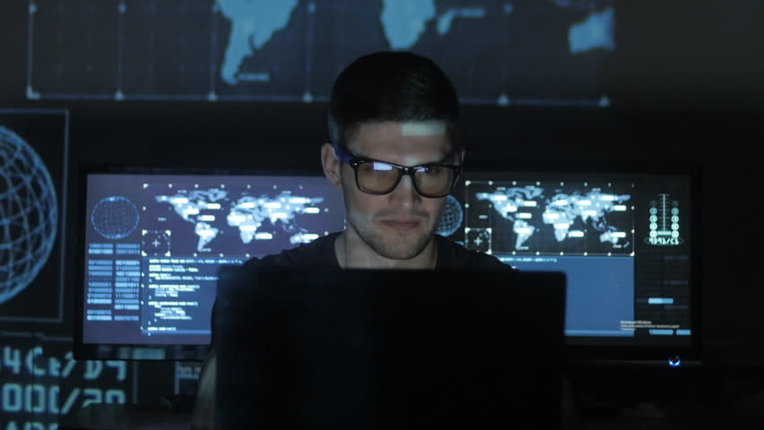 Hacker programmer in glasses is working on computer while blue binary code characters reflect on his face in cyber security center filled with display screens. | Shutterstock HD Video #1008776846