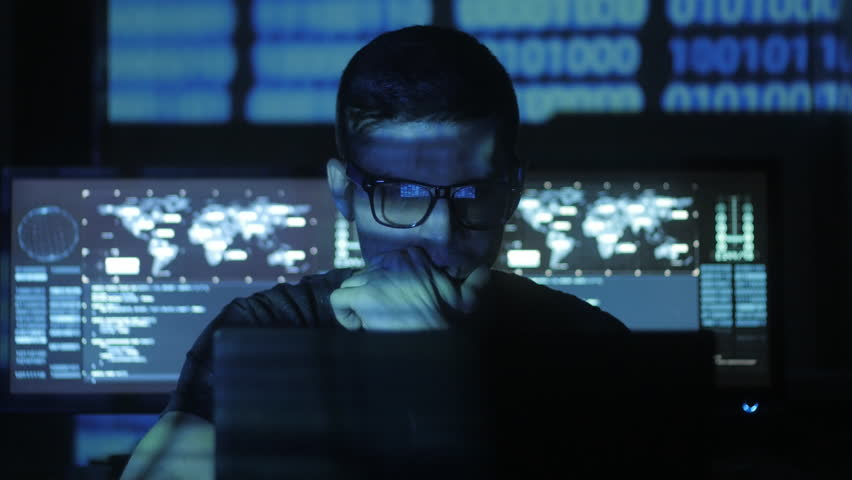 Hacker programmer in glasses is working on computer while blue binary code characters reflect on his face in cyber security center filled with display screens. | Shutterstock HD Video #1008780386