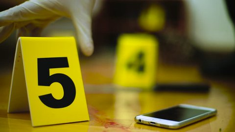Hands of police detective placing evidence markers by the blood traces of homicide during crime scene investigation, smartphone ringing in focus, concept mystery, murder, csi, close up, room interior.