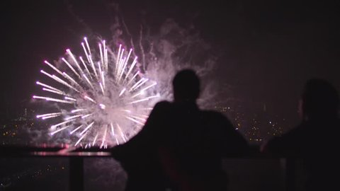 People look at the fireworks from the roof of skyscraper. Colorful flash at a very close distance. Spectacular concept of celebration, success, happiness. 4K