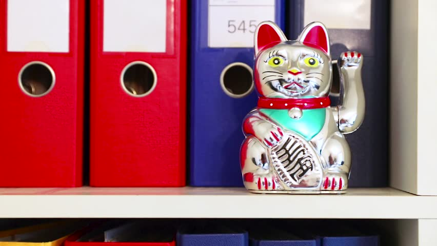 Silver plastic beckoning cat or Maneki-neko on shelf with ring binders