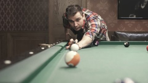 a man in a plaid shirt playing billiards
