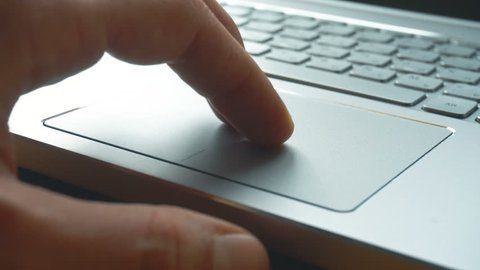 Laptop keyboard. Close up shot of man scrolling a Website Using Laptop Track Pad