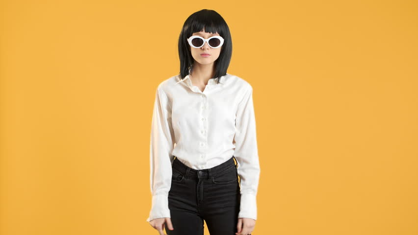 Portrait closeup of happy stylish female with bob hairdo wearing fancy sunglasses dancing energetic disco in 60's, over yellow background. Concept of emotions