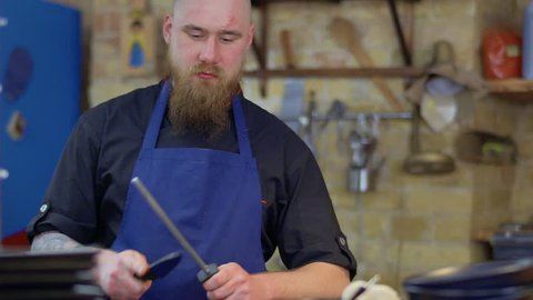 Muscular tattooed chef with sharp knife in Korean restaurant