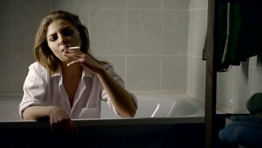 A young woman is in a bath, she smokes a cigarette and enjoys inhaled smoke | Shutterstock HD Video #1008810686