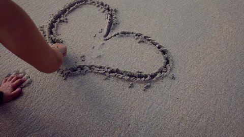 Happy girl draws on a sandy beach heart, makes a confession. slow motion, 1920x1080, full hd