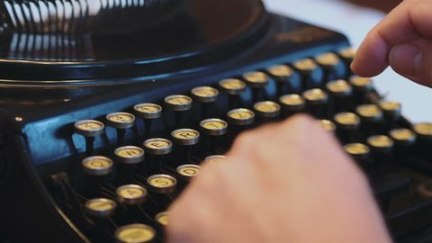 Professional video of senior man typing on an old typewriter in 4k slow motion 60fps