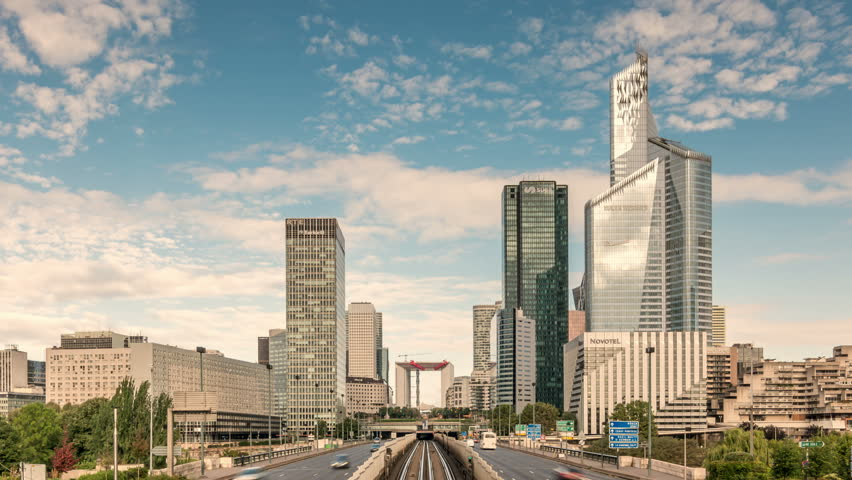 Car traffic in modern district La Defense in Paris. Clouds move across the blue sky. Zoom out shot. | Shutterstock HD Video #1008850436