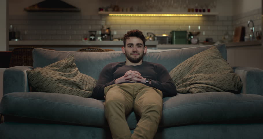 Man walks into the living room and sits on a couch to watch tv