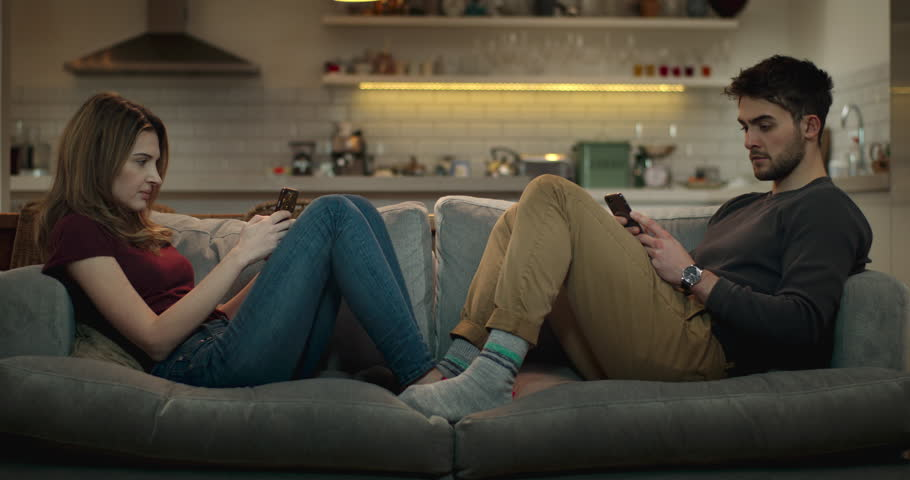 Man and woman ignore each other on the sofa while using their smartphones for social media.
