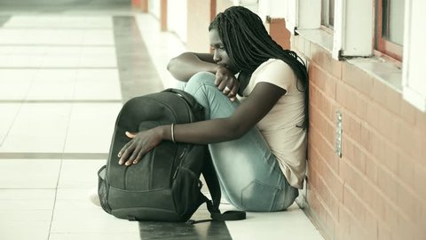 African female teenager alone in school hallway and sad. Vintage filtered. Bullying concept.