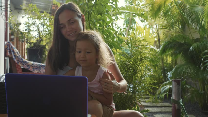 Young woman with little cute daughter using laptop together in slow motion. They sits at the table at domestic garden and talk on video and waves by they hands.