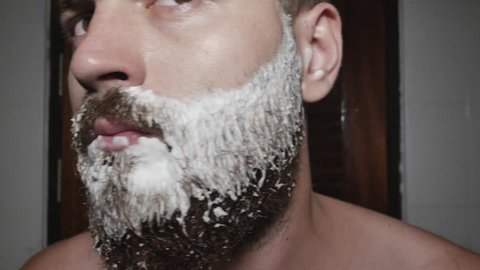 Close up of a handsome young man shaving his beard at the bathroom using a razor shaving. A man with foam on his face using razor to shave off beard. Brutal man with big beard