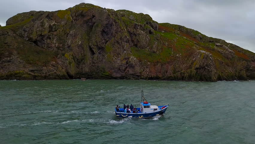 Aerial view of boat with unrecognizible people in sea sailing near the Ireland`s Eye island, Howth, Ireland   Shutterstock HD Video #1008874796