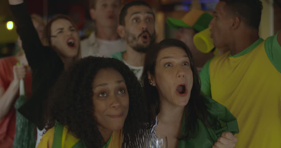 Brazilian football fans celebrating victory in sports bar, slow motion