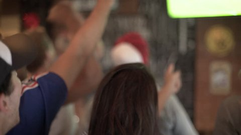 Football fans cheering while watching televised match at sports bar