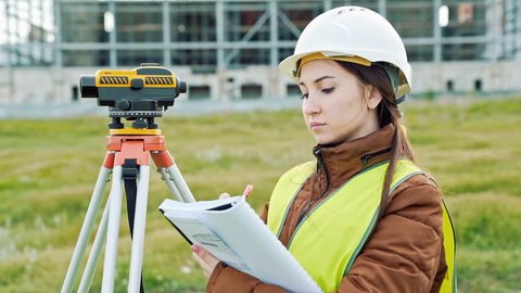 A young woman surveyor in work clothes and helmet adjusts the equipment and produces calculations on the construction site. The concept of landscape design, geodesy