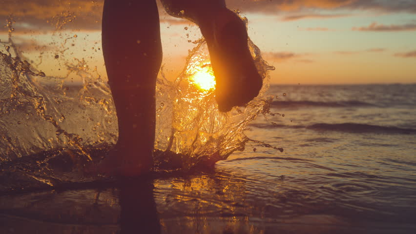 SLOW MOTION, CLOSE UP, COPY SPACE: Unrecognizable woman tourist runs into shallow ocean water at idyllic exotic sunset. Carefree girl on tropical beach runs into refreshing sea at golden sunrise.