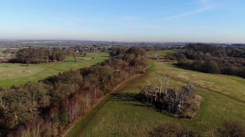 English Countryside In Winter Aerial View, Blue Sky Wooded Road, Camera Pan In, Dynamic Moving Shot, Village And City In Distance