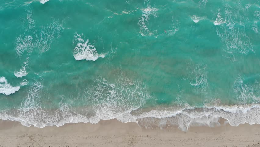 Rough wall of waves crashing view from an aerial perspective looking down at the shoreline in Miami Beach | Shutterstock HD Video #1008943586