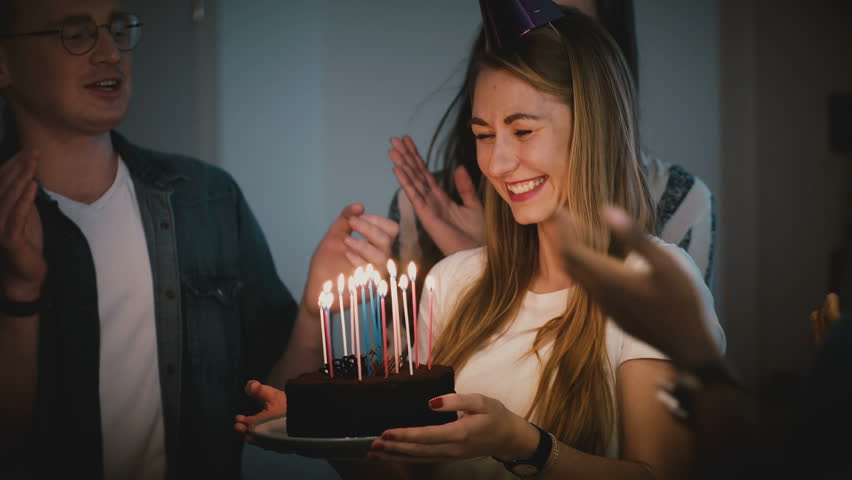 Beautiful woman makes a wish and blows on candles. Diverse multi ethnic group celebrate birthday party together. 4K. | Shutterstock HD Video #1008959726