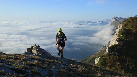 Athlete trail running in the mountains on a beautiful morning. Vercors, France.