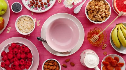 Granola with natural yogurt, fresh raspberries, honey, almond flakes and poppy seeds in a ceramic bowl on a pink wooden table, top view. Healthy eating concept, perfect breakfast or dessert.