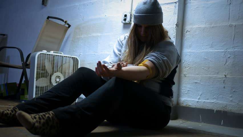 A Woman injects herself with a heroin needle in a trap house