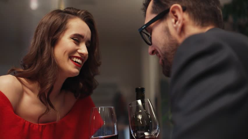 Cute happy Ukrainian girl with dimples smiling and talking with likable man. Young couple in love drinking red wine in restaurant. Blind date. Love story.