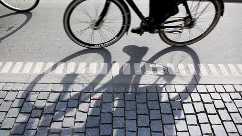 People cycling in Copenhagen, focus on bicycle shadows. Side view of a bicycle lane in the Danish capital, with many persons commuting by bike.