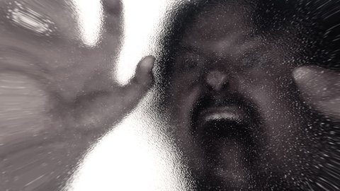 Lens distorted scene: a zombie lurking behind a frosted glass door and attacking the viewer. Horror Halloween themed shot.